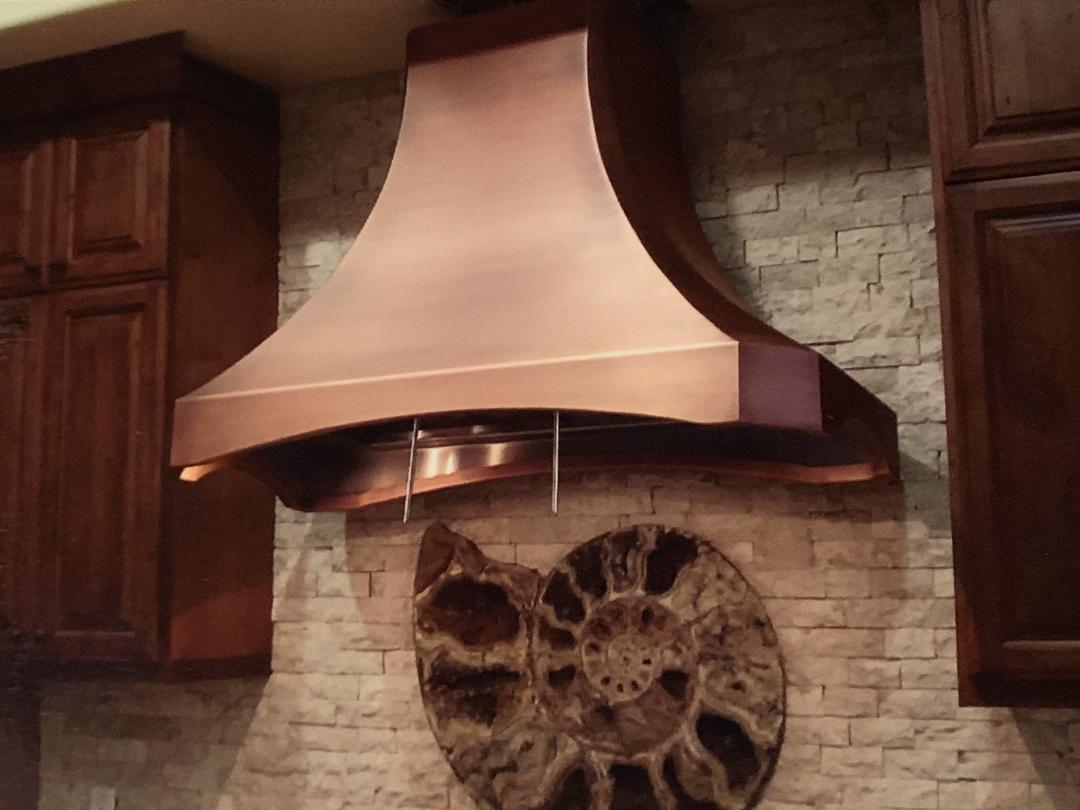 copper kitchen hood with a sea shell